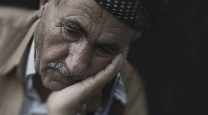Elderly man resting his face in his hand
