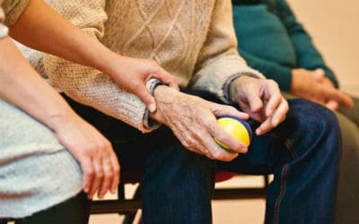 an older man sitting on bleacher holding a stress ball with a younger caretaker assisting