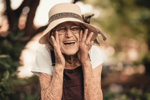 an older woman in a floppy straw hat smiling with her hands cupping her face