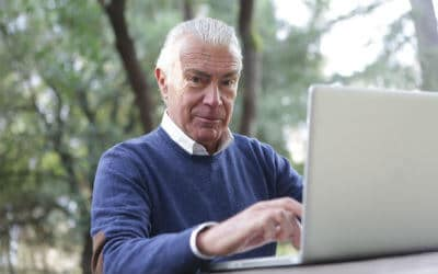 an older man typing on a computer